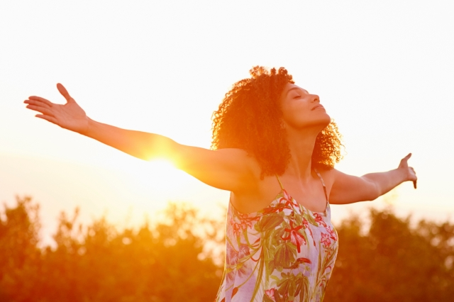 Woman outstretched arms in an expression of freedom with sunflar